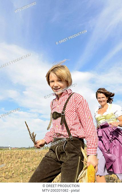 Mother and son running in cornfield, Bavaria, Germany