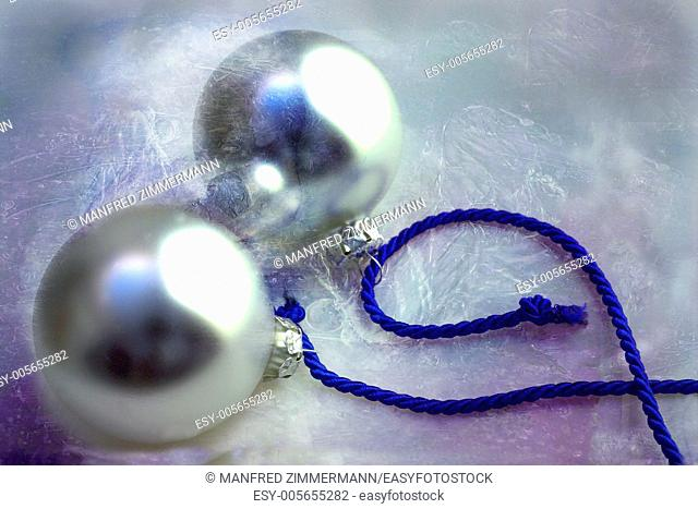 Two silver Christmas baubles on blue ribbon