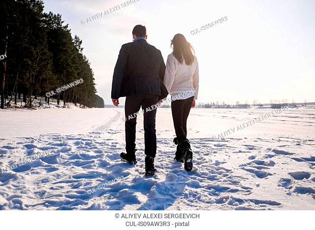 Young couple walking on snow-covered field