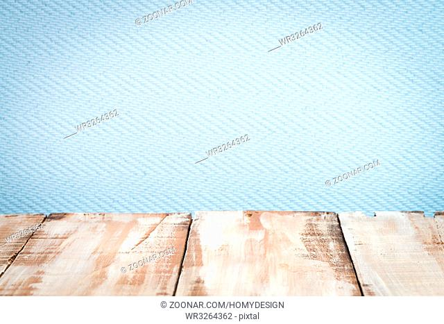 Wooden table top with blue wall background