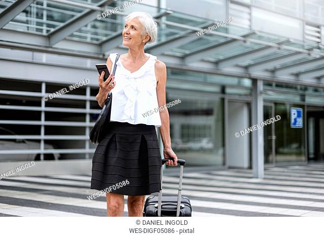 Smiling senior woman with cell phone and baggage on the move