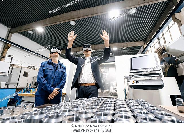 Businessman and skilled worker in high tech enterprise, using VR glasses