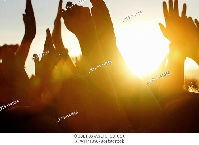 sun setting at open air concert through fans waving their arms in the air