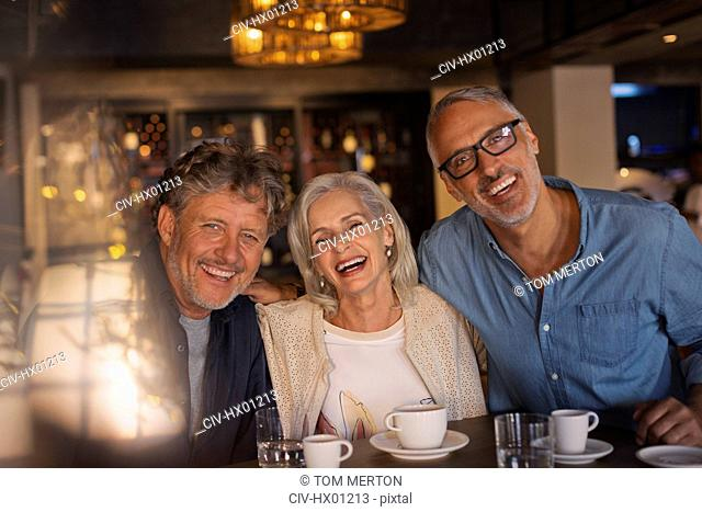 Portrait laughing friends drinking coffee in restaurant
