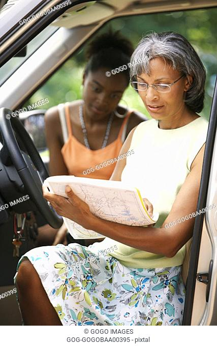Middle-aged African woman reading a map in car