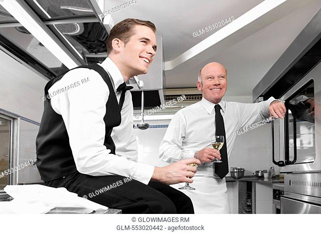 Two waiters drinking wine in the kitchen