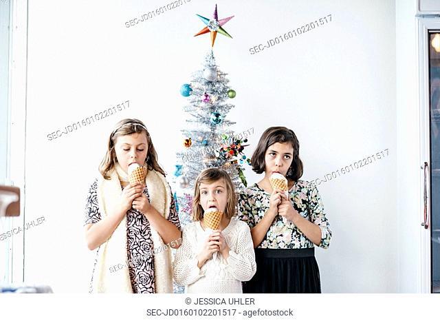 Girls eating ice cream next to christmas tree