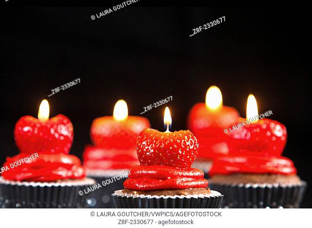 Strawberries are used as traditional birthday candles for chocolate cupakes instead of regular candles