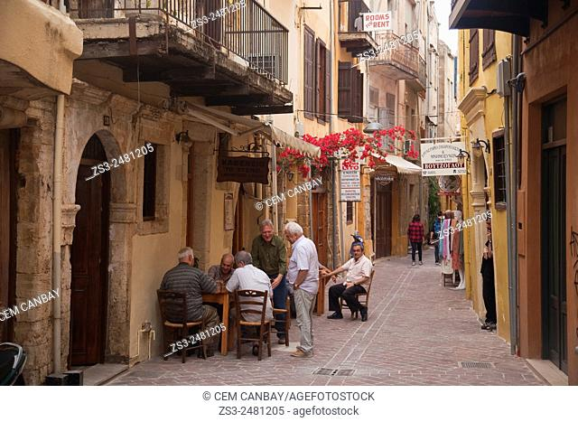 Street scene from the old town with people playing backgammon in the foreground, Chania, Crete, Greek Islands, Greece, Europe