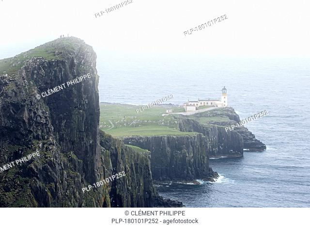 Walkers on clifftop watching Neist Point Lighthouse in the mist on the Isle of Skye, Inner Hebrides, Scottish Highlands, Scotland, UK