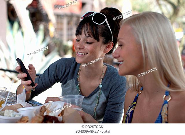 Girlfriends looking at mobile phone in outdoor cafe