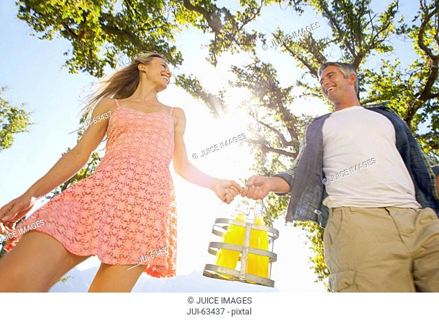 Couple walking with picnic bottles in countryside