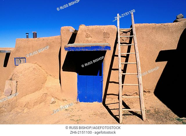 Ladder and adobe house with blue door, South House (World Heritage Site), Taos Pueblo, New Mexico USA
