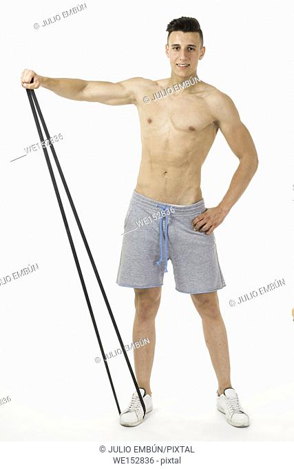 Muscular young sportsman exercising on white background
