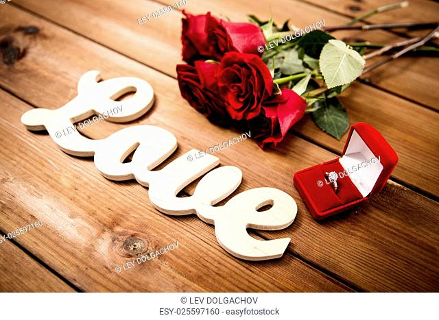 proposal, romance, valentines day and holidays concept - close up of gift box with diamond engagement ring, red roses and word love on wood (vintage effect)