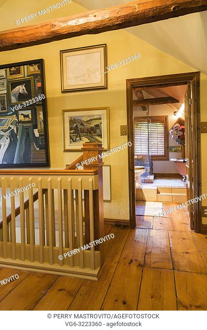 Opened main bathroom door plus railing surrounding the staircase on the hallway on the upper floor inside an old circa 1850 Canadiana cottage style home