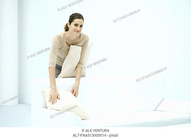 Woman arranging pillows on sofa, smiling at camera
