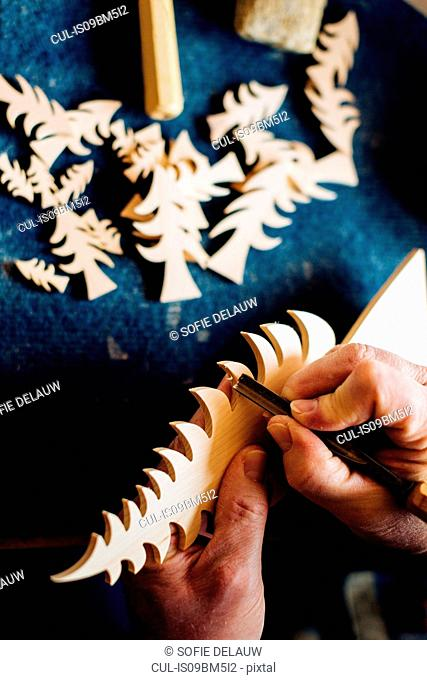 Carpenter chiseling edge of wooden christmas tree at workbench, close up of hands