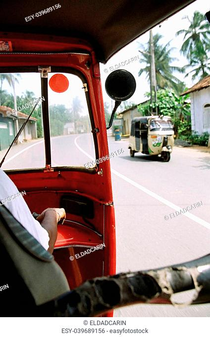 A view at a road in Sri-Lanka, from inside a rikshaw