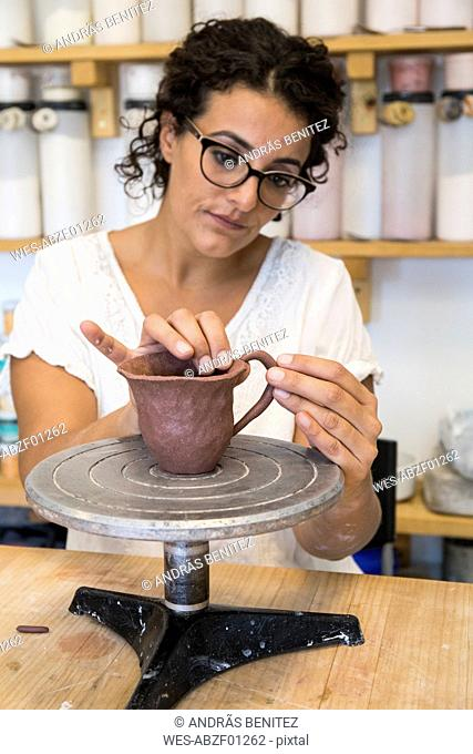 Woman placing the handle of a cup of clay in a ceramic workshop