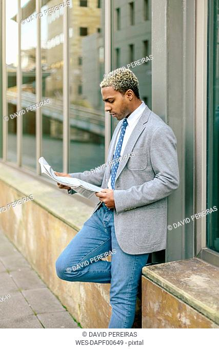 Businessman leaning against wall, reading newspaper