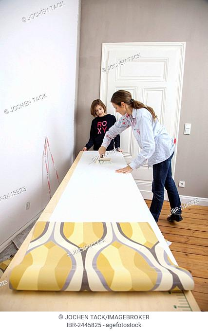 Mother and daughter renovating a room, preparing wallpaper for wallpapering a wall