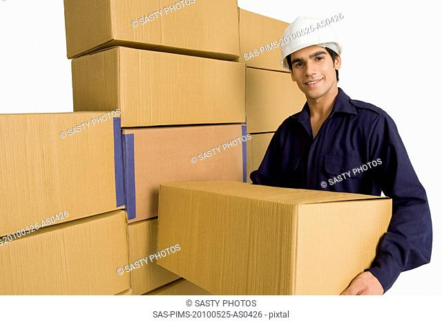 Store in charge carrying a cardboard box in a warehouse