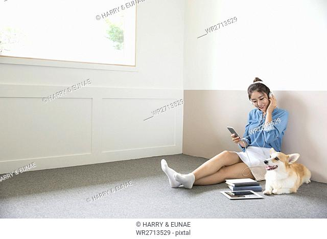 Woman with pet dog listening to music