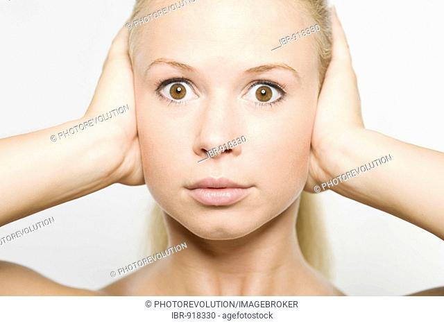 Young blonde woman covering her ears