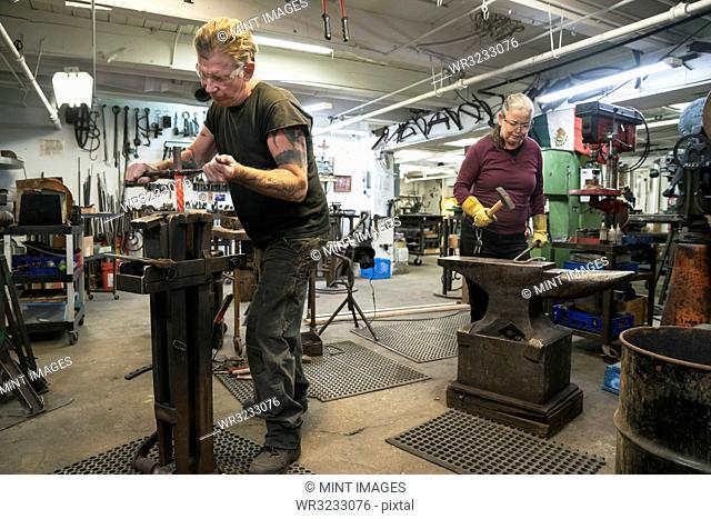 Caucasian male and female blacksmiths, metalworkers at work in their studio workshop
