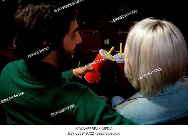Couple toasting drinks while watching movie in theatre