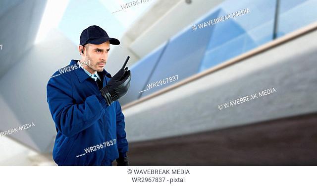 Security guard talking on walkie talkie while standing against defocused building