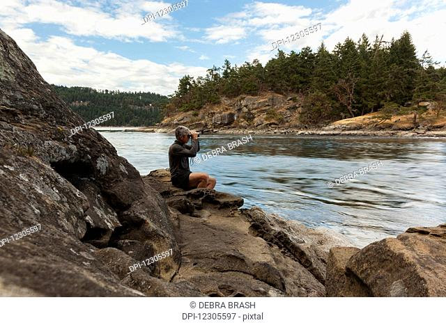 A senior man watches the tides at Dodds Narrows on Vancouver Island; British Columbia, Canada