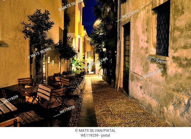 Old alley illuminated at night with chairs and tables