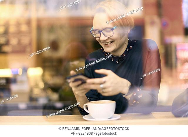 laughing woman in coffee shop with smartphone in hand, in Munich, Germany