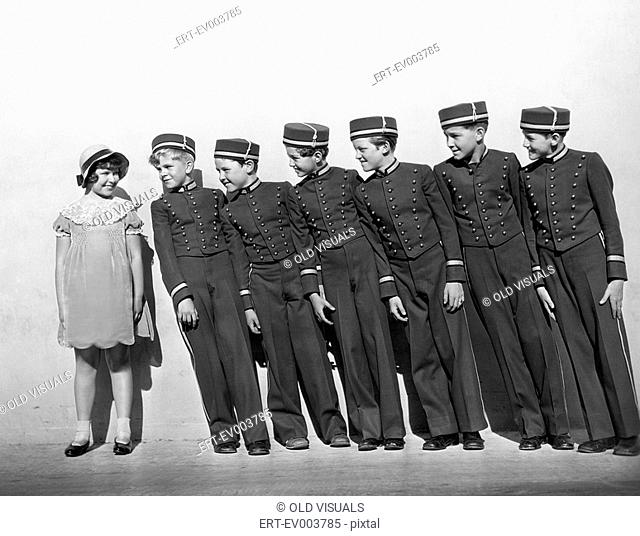 Line of young bellhops smiling at girl All persons depicted are not longer living and no estate exists Supplier warranties that there will be no model release...