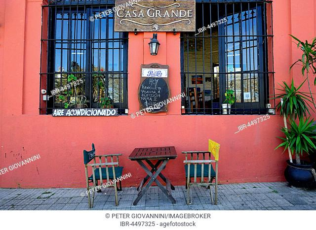 Table with chairs in front of a restaurant with red facade, Colonia del Sacramento, Colonia, Uruguay