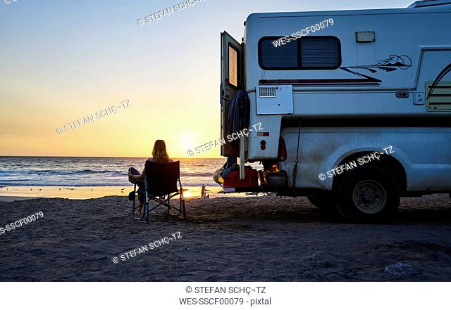 Chile, Arica, woman sitting next to camper on the beach at sunset