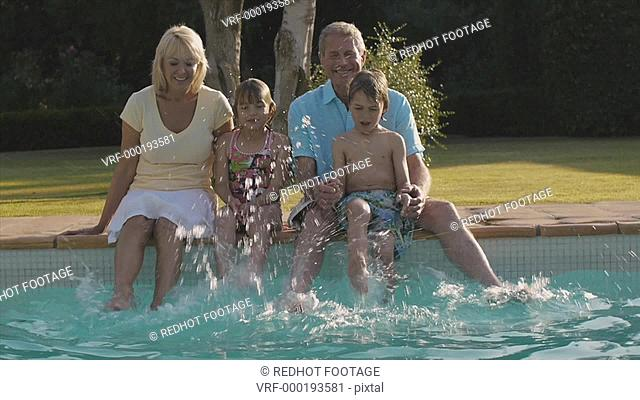 Slow motion of grandchildren and grandparents sitting on side of pool splashing their feet in water