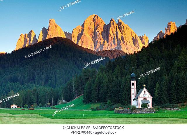 Funes valley, Dolomites, Trentino Alto Adige, Italy. The picturesque small church San Giovanni in Ranui at under of Odle at sunset