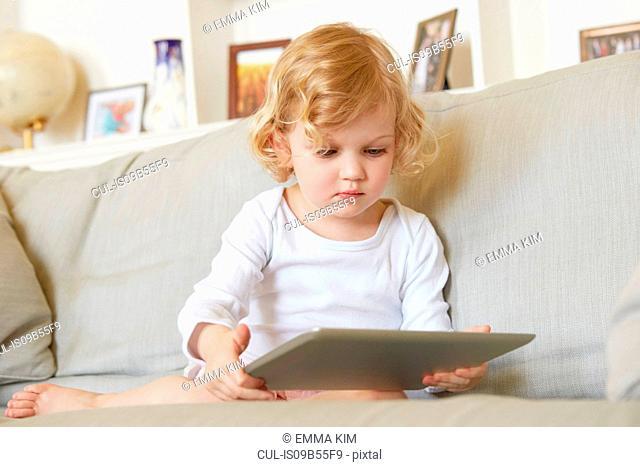 Female toddler sitting on sofa using digital tablet