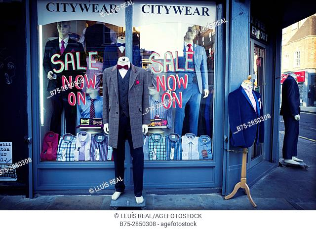 "Facade of a clothing store with several mannequins dressed in fashionable clothes and a ""Sale"" sign. Petticoat Lane Market, East End, London, England"