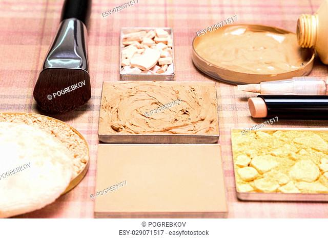 Makeup products to create beautiful skin tone: concealers, cream-to-powder and liquid foundation, shimmer powder golden color