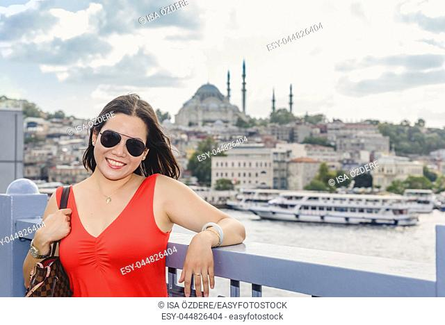 Beautiful Chinese woman poses over Galata Bridge with view of Suleymaniye mosque on background