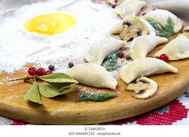 Traditional Russian food dumplings or vareniki, dough with meat or other stuffing, with flour and egg served on a table with sour cream