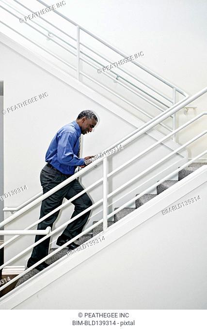 Black businessman climbing staircase