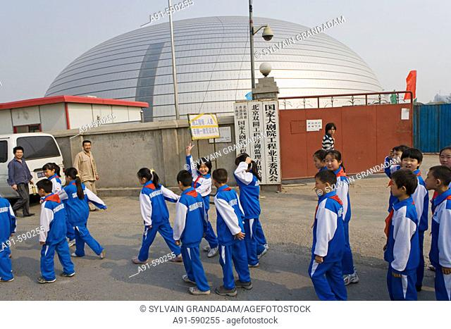 Scholars in uniform passing by the new National Opera House building site by Tianenmen square (Paul Andreu architect).Beijing. China