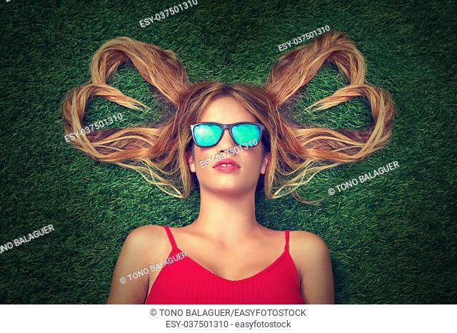 Blond teen girl with hair heart shapes lying down on turf with sunglasses