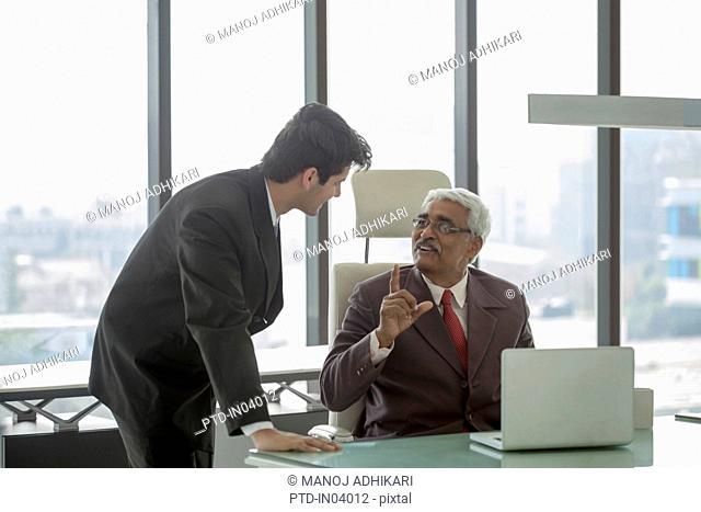 India, Senior businessman explaining something to younger man