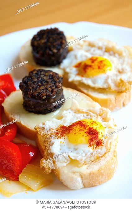 Spanish tapa: Bread with cheese, morcilla and fried quail egg